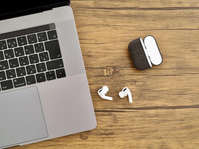 ノートパソコンとワイヤレスイヤホンが並んでいる画像