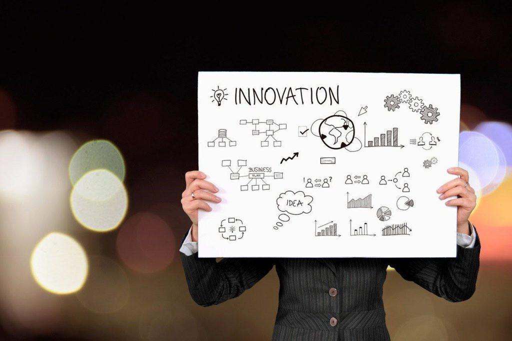 イノベーションと書かれた紙を持っている男性の画像
