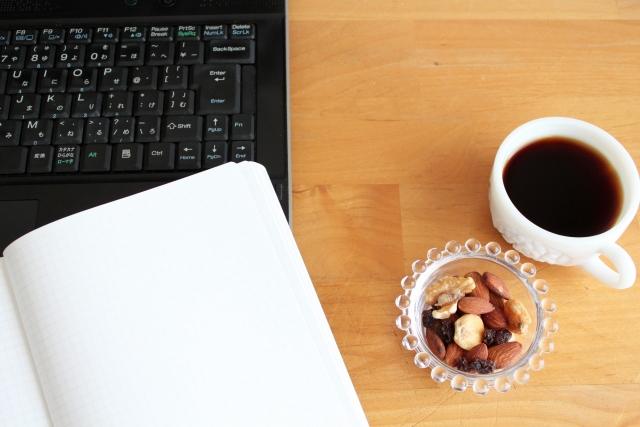 パソコンとノートとコーヒーが並んでいる画像