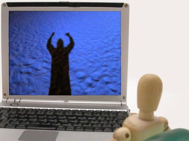 人形がパソコンの画面を見ている画像