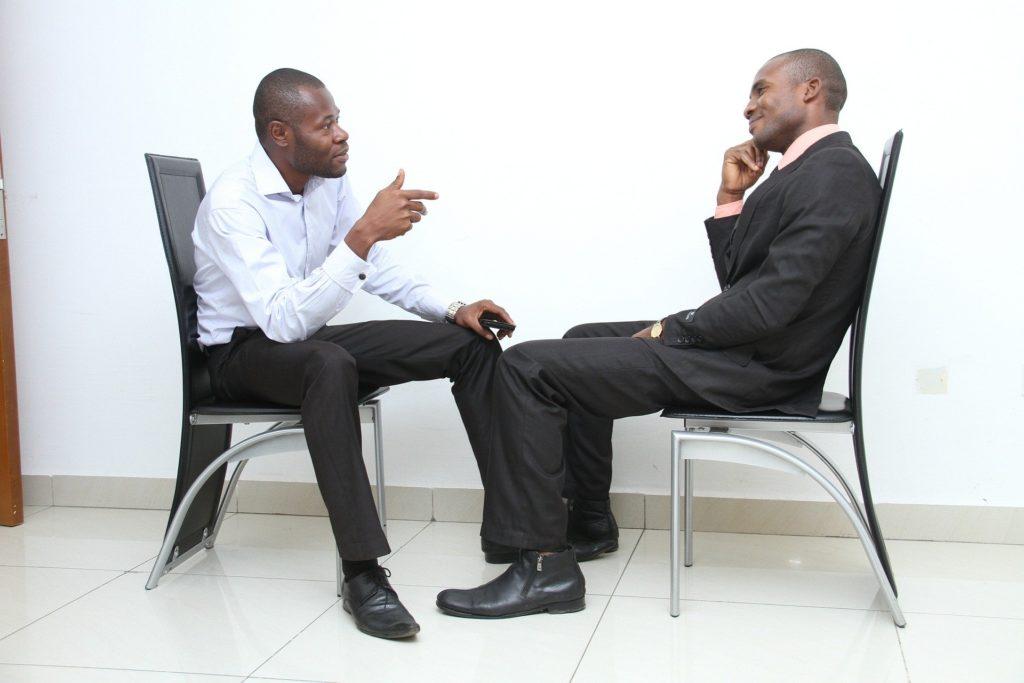 男性が向かい合って話している画像