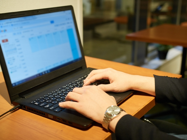 ノートパソコンを使っている女性の画像