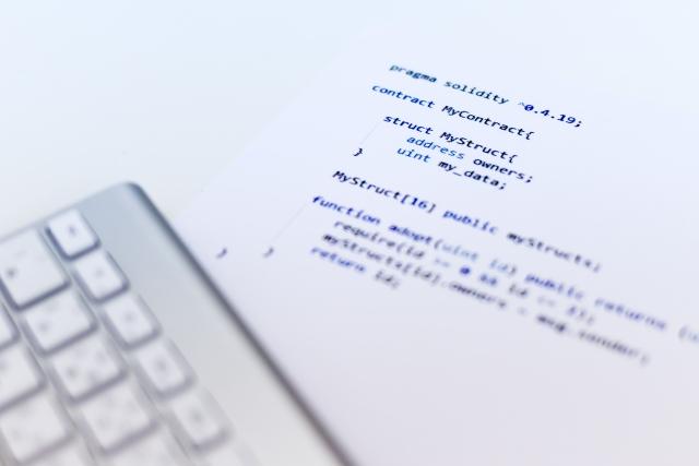 プログラムコードが書かれた紙とノートパソコンの画像