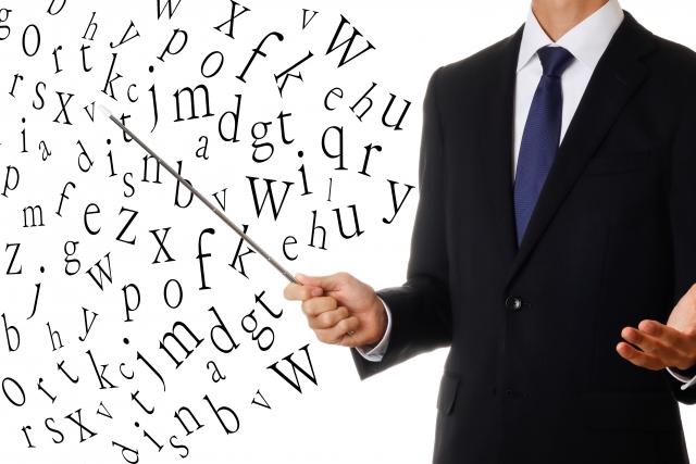 アルファベットを棒で指している男性の画像
