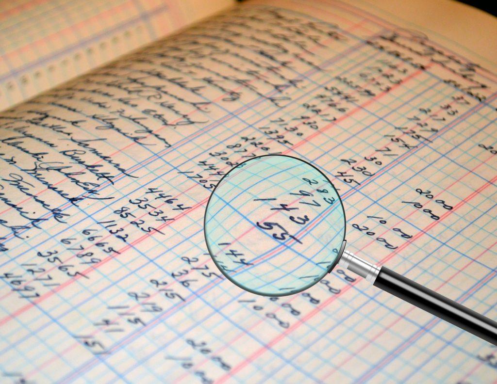 虫メガネで家計簿を見ている画像