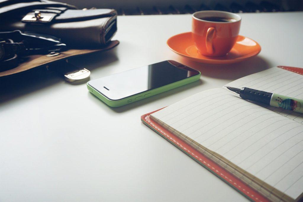 スマートフォン・ペン・コーヒーが並んでいる画像