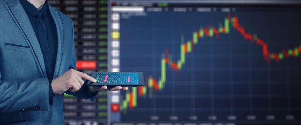 株式チャートの前でタブレットを操作している男性の画像