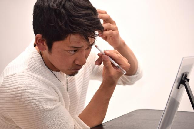 眉毛を書いている男性の画像