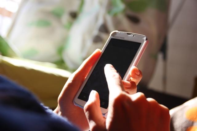 携帯を操作している画像