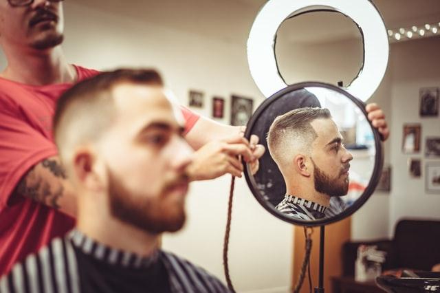 鏡越しで髪型を確認する男性の画像
