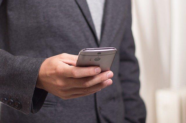 スマートフォンを持っている男性の画像