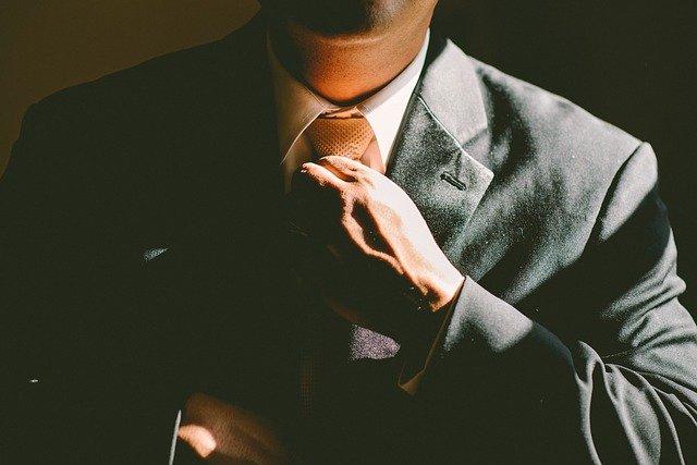 ネクタイを握っている男性の画像