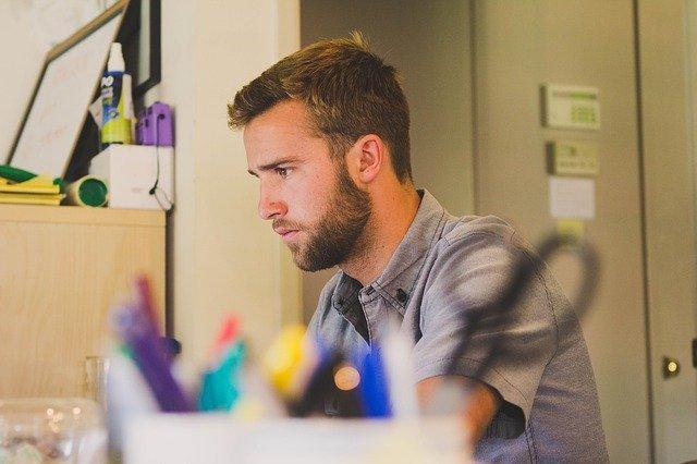 机に向かっている男性の画像